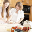 Baking. Caucasian mother and daughter in the kitchen kneading dough to make a fruit dessert - Stock Photo
