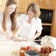 Stock Photo: Baking. Caucasimother and daughter in kitchen kneading dough to make fruit dessert