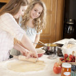 Baking. Caucasian teenage girlfriends rolling dough to make a fruit pie with homegrown fruits in the kitchen — Stock Photo