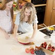 Baking: Caucasian caucasian teenage girlfriends making a fruit pie with homegrown fruits in the kitchen — Stock Photo #21374741