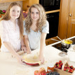 Baking: Caucasian caucasian teenage girlfriends making a fruit pie with homegrown fruits in the kitchen — Stock Photo #21374749