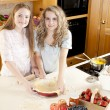 Stock Photo: Baking: Caucasian caucasian teenage girlfriends making a fruit pie with homegrown fruits in the kitchen