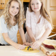 Baking. Caucasian teenage girlfriends making a fruit pie and pastry with homegrown fruits in the kitchen — Stock Photo