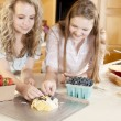 Stock Photo: Baking. Caucasian teenage girlfriends making a fruit pie and pastry with homegrown fruits in the kitchen
