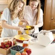 Baking: Caucasian caucasian teenage girlfriends making a fruit pie with homegrown fruits in the kitchen - Stock Photo