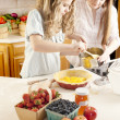 Baking: Caucasian caucasian teenage girlfriends making a fruit pie with homegrown fruits in the kitchen — Stock Photo #21374797