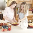 Baking: Caucasian caucasian teenage girlfriends making a fruit pie with homegrown fruits in the kitchen — Stock Photo #21374801