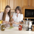 Canning. Caucasimother and teenage daughter canning homegrown fruits and vegetables — Stock Photo #21374809