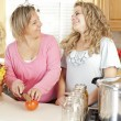 Canning. Laughing caucasian laughing mother and teenage daughter canning homegrown fruits and vegetables — Stock Photo #21374849