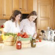 Canning. Caucasimother and teenage daughter canning homegrown fruits and vegetables — Stock Photo #21374869