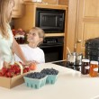 Canning. Mother and son canning homegrown fruits for preserves — Stock Photo #21374895