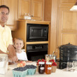 Canning. Father and son canning homegrown fruits for preserves — Stock Photo #21374919