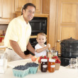 Canning. Father and son canning homegrown fruits for preserves — Stock Photo #21374943