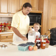 Canning. Father and son canning homegrown fruits for preserves — Stock Photo #21374947