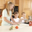 Canning. Mother and her two sons canning homegrown fruits and vegetables — Stock Photo #21375043