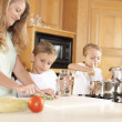 Canning.  Mother and her two sons canning homegrown fruits and vegetables — Stock Photo