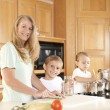 Canning. Mother and her two sons canning homegrown fruits and vegetables — Stock Photo #21375073