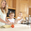 Stock Photo: Canning. Mother and her two sons canning homegrown fruits and vegetables