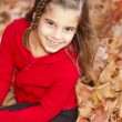 Smiling caucasilittle girl in seasonal autumn leaves — Stok Fotoğraf #21375109