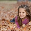 Laughing caucasilittle girl lying down in autumn leaves — Stok Fotoğraf #21375111