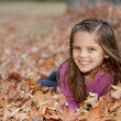 Laughing caucasilittle girl lying down in autumn leaves — Stockfoto #21375111
