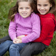 Smiling caucasian little girl sisters sitting togetter outdoors - Stock Photo