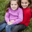 Smiling caucasilittle girl sisters sitting togetter outdoors — Stock Photo #21375135