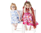 Two sisters sitting together playfully in dress up clothes — Stock Photo