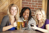 Women enjoying a girl's night out together at a restaurant bar — Stockfoto