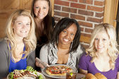 Image of a young adult group of women eating at restaurant — Стоковое фото