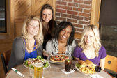 Adult roup of women friends eating together at a restaurant — Stock Photo