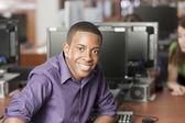 Educación. estudiante de secundaria adolescente negro usando una computadora en la biblioteca de la escuela — Foto de Stock