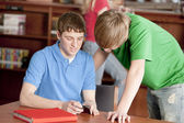 Dospívající středoškolských studentů studuje ve školní knihovně — Stock fotografie