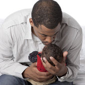 African american father kissing his newborn baby son — ストック写真