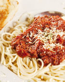 Food and Drink. Closeup image of a hearty spaghetti dinner with garlic bread — Stock Photo