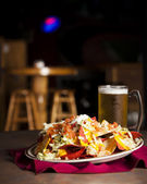 Food and Drink. An appetizer of spicy nachos with a frosty mug of beer — Stock Photo