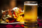 Food and Drink. A closeup image of spicy nachos with a cold, frosty mug of beer. — Stock Photo