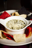 Food and Drink. An appetizer of cheesy spinach and artichoke dip with tortilla chips — Stock Photo
