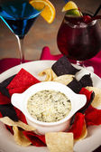 Food and Drink. An appetizer of cheesy spinach and artichoke dip with tortilla chips and cocktails. — Stock Photo