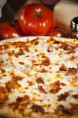 Food and Drink. A zesty all meat pizza. — Stock Photo