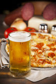 Food and Drink. A zesty all meat pizza with a cold mug of beer. — Stock Photo