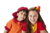 Real. Smiling caucasian brother and sister wearing a bright red and orange clothing — Stock Photo