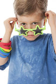 Real. Unhappy caucasian little boy peeking over his star shaped sunglasses — Stock Photo
