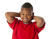 Real. Black little boy wearing a bright red shirt with his hands resting behind his head — Stock Photo
