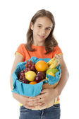 Healthy Eating. Caucasian little girl holding a basket with an arrangement of fruit — Stockfoto