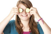 Healthy Eating. Caucasian girl holding cucumbers up to her eyes — Stock Photo