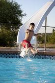 スイミングを夏します。水スライドの夏の太陽で楽しんでいるヒスパニック男の子 — ストック写真