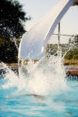 Summer Swimming. Child having fun in the summer sun by making a big splash on a water slide — Stock Photo