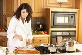 Verkliga. blandras ung vuxen kvinna matlagning en hälsosam måltid i hennes kök — Stockfoto