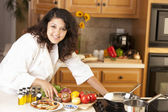 Real. Mixed race young adult woman cooking bruschetta and a healthy meal in her kitchen — Stock Photo